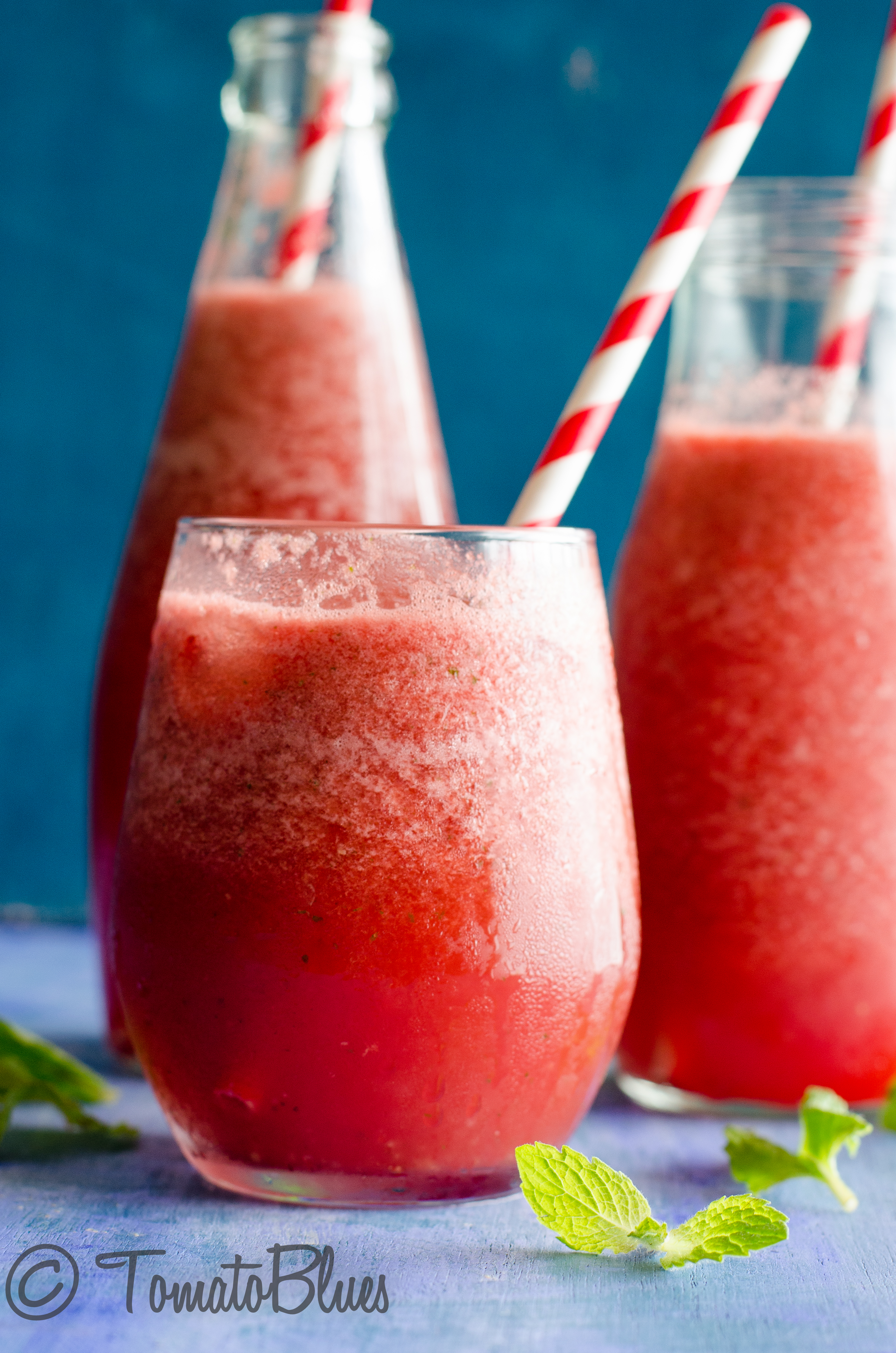 mexican watermelon agua fresca served in glasses and bottles with red and white straws