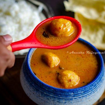 paruppu urundai kuzhambu- South Indian lentil ball gravy served in a white blue bowl.