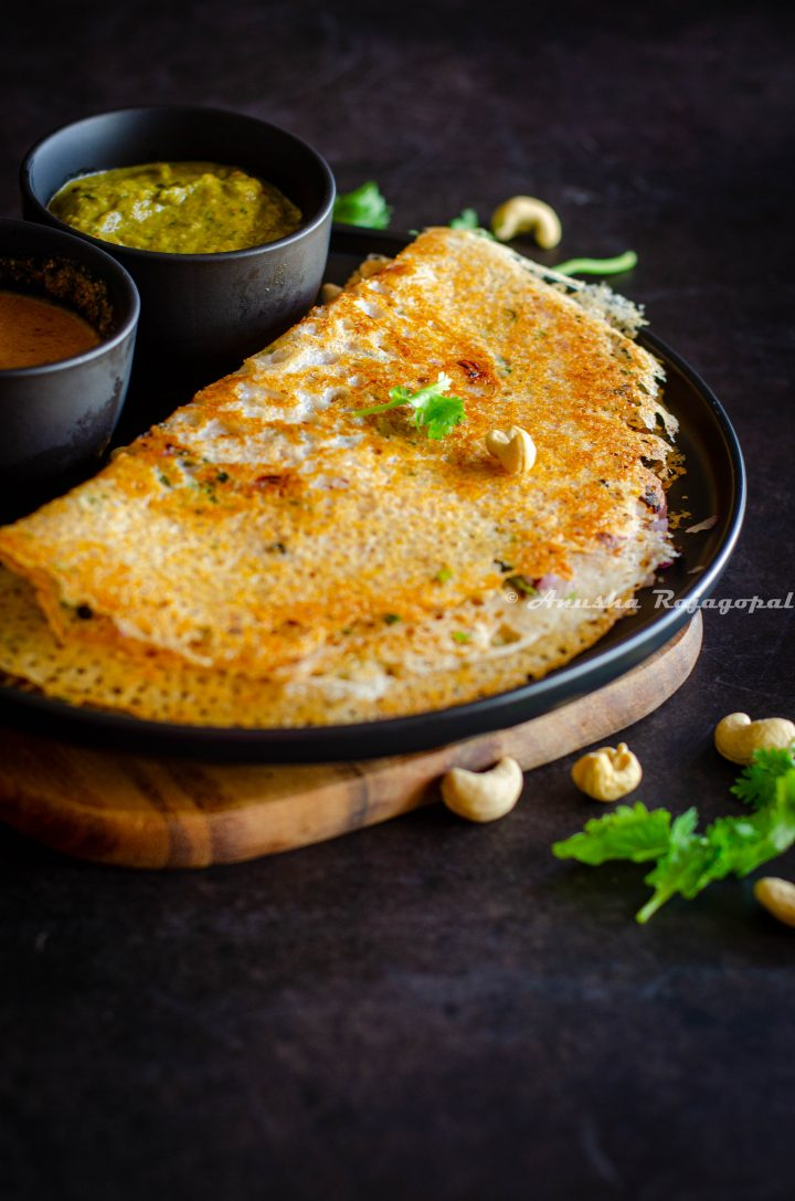 crispy Instant rava dosa served with chutney by the side on a black plate. Coriander leaves and cashews sprinkled on the top and by the side.