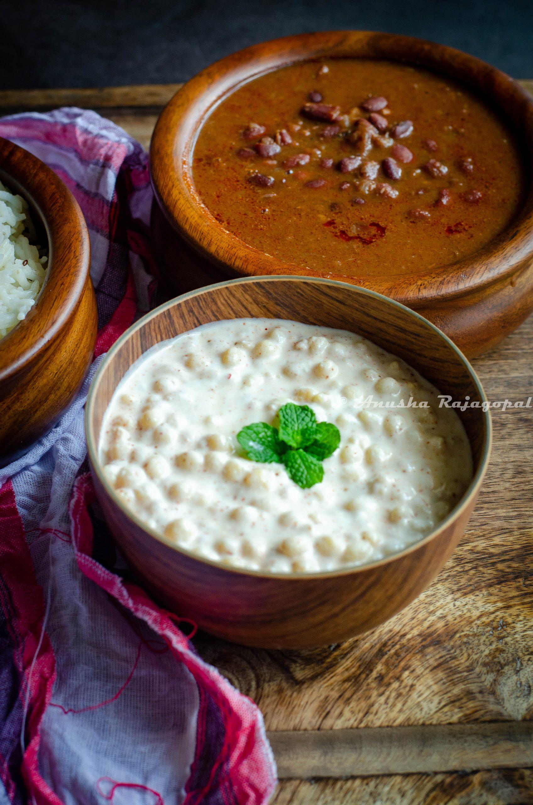Boondi raita served in a wooden bowl alongside rajma masala