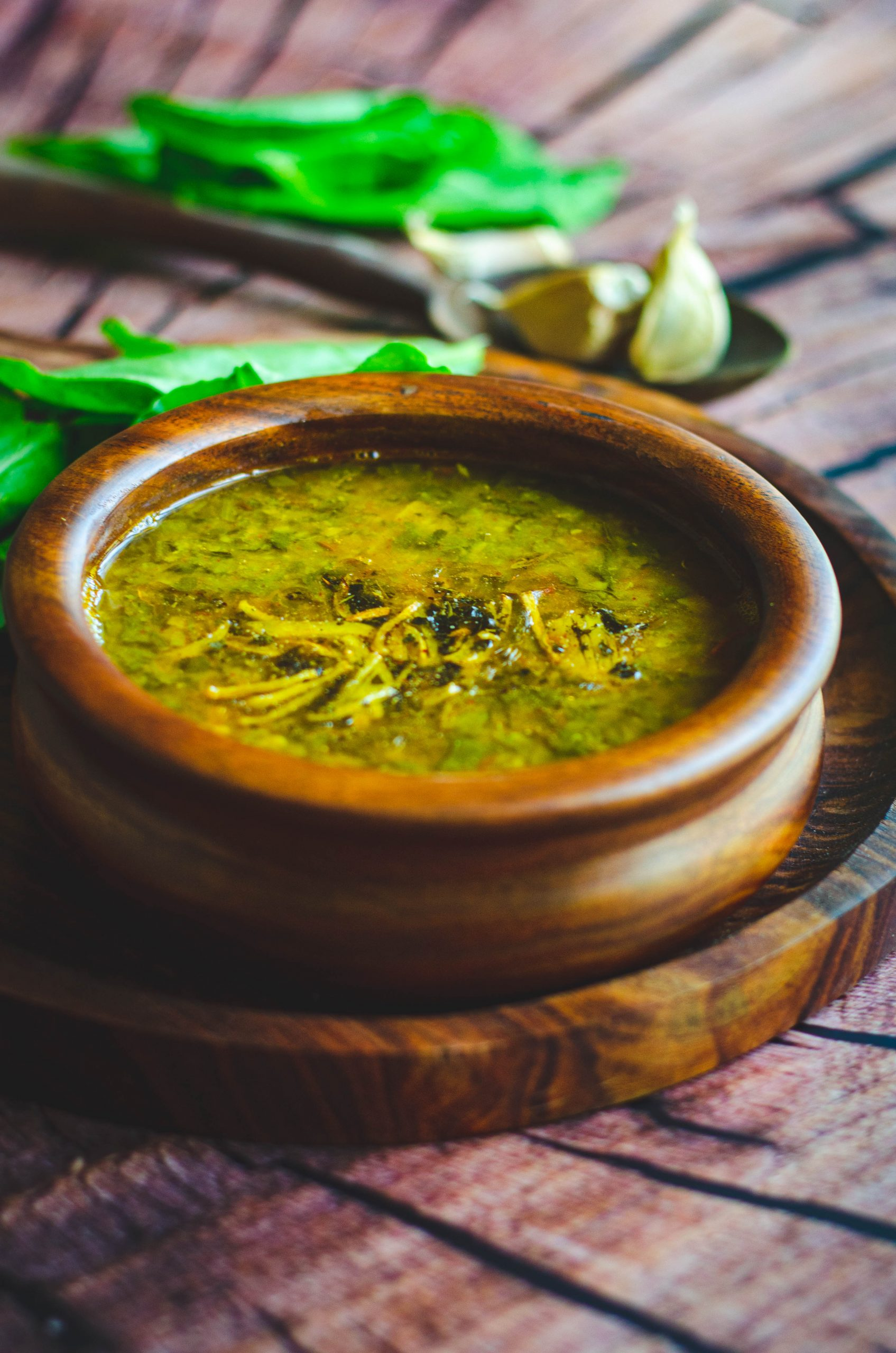 Spinach garlic dal served in a wooden bowl placed on a wooden plate