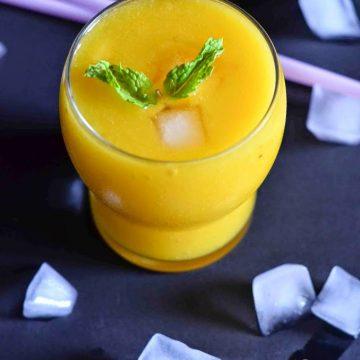 mango peach smoothie served with ice cubes around it