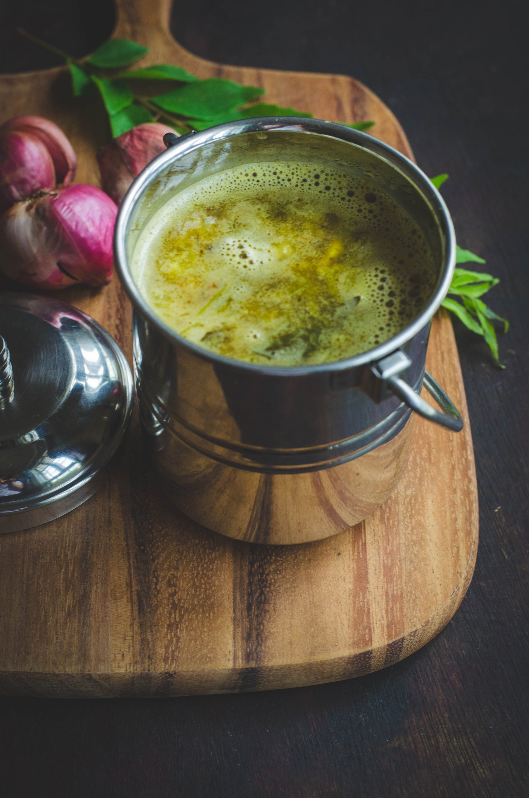 Onion rasam served in a stainless steel handled container placed on a wooden board