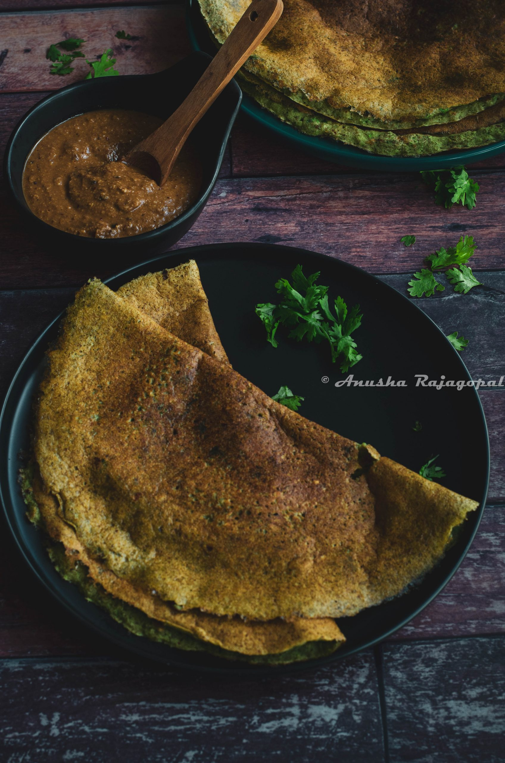 pesarattu- high protein moong beans dosa served on a black plate placed on a table.