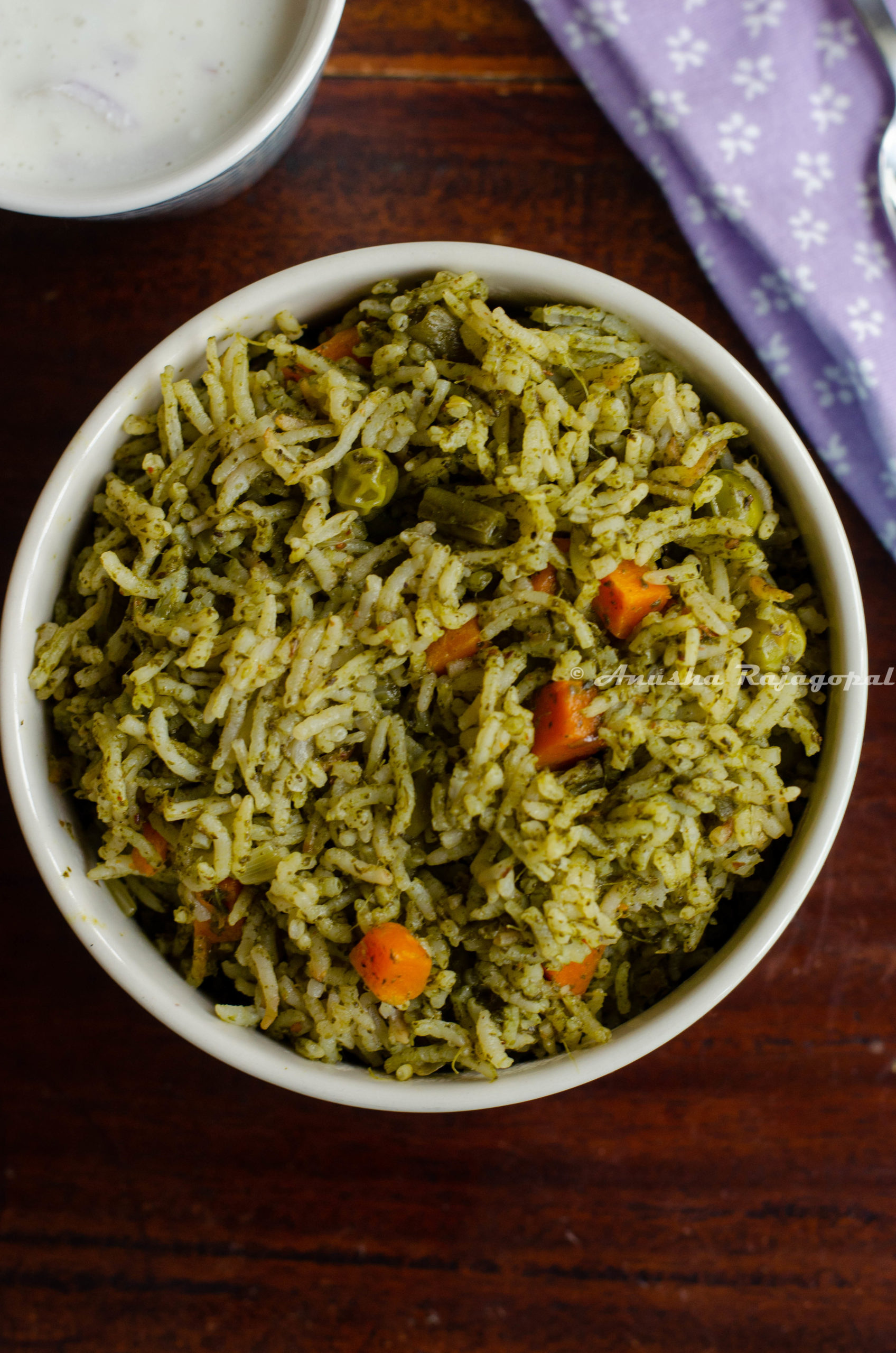 spinach pulao made in the instant pot and served in a blue bowl with raita