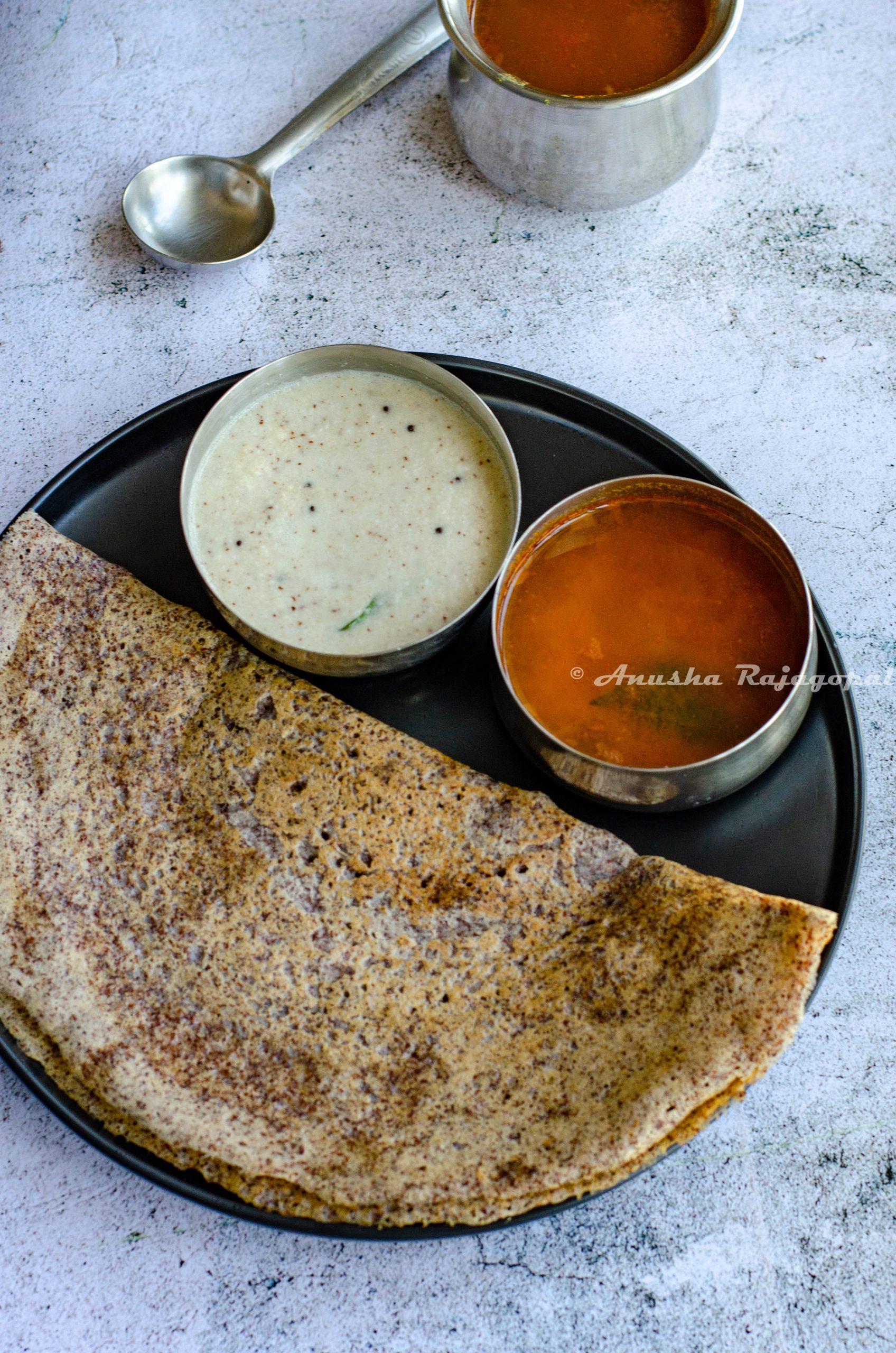 Ragi dosa served with coconut chutney and sambar on a black plate