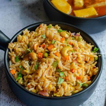 vegan thai basil fried rice served in a black handled bowl alongside orange tofu