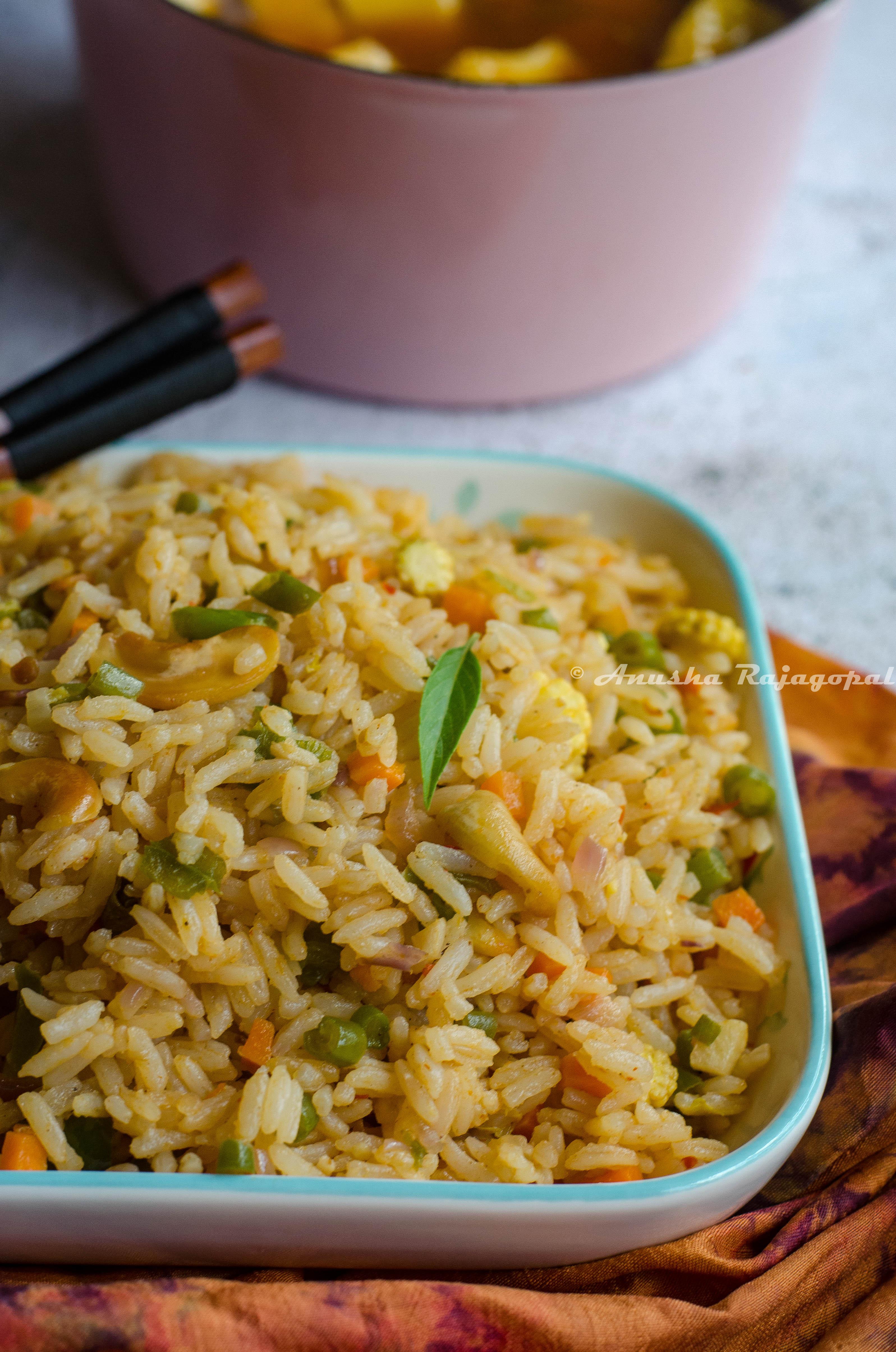 vegan thai basil fried rice served in a white platter placed on a tye dye napkin