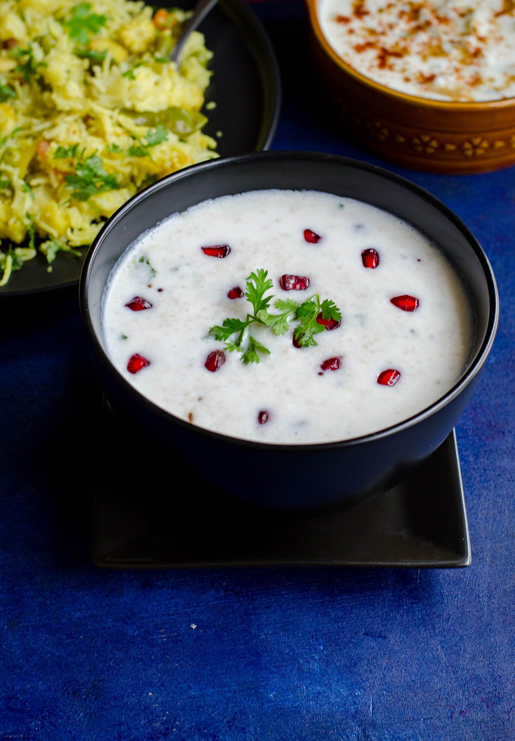 Samai Thayir Sadam served in a black bowl. Pomegranate pearls and cilantro as garnish.