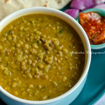 Instant pot green moong dal served in a blue bowl with rotis