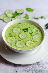 cucumber gazpacho topped with cucumber slices and herbs served in a white bowl set against a white background