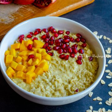 vegan mango overnight oats topped with pomegranate pearls and mangoes