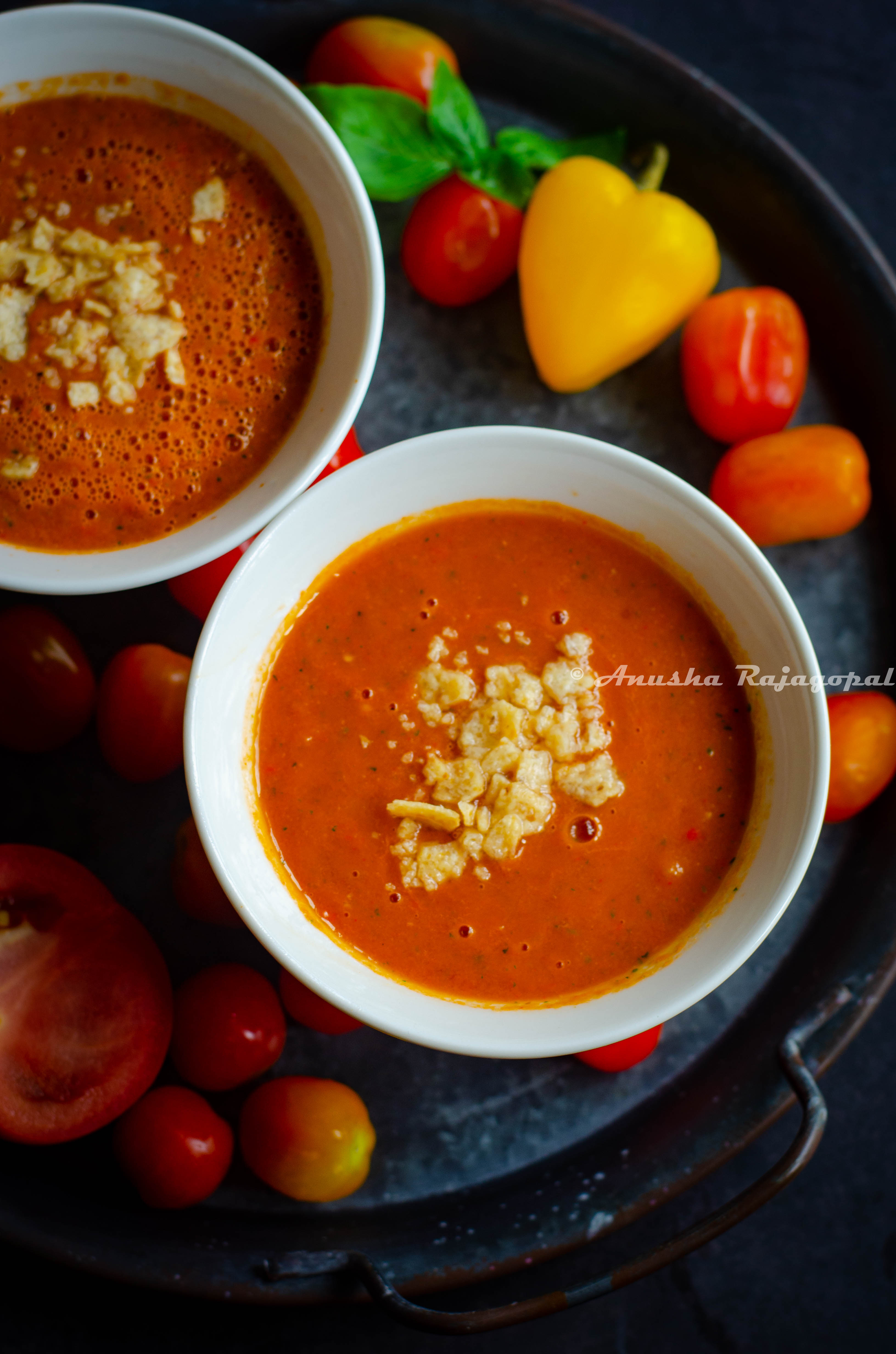 raw vegan tomato gazpacho served in soup bowls with sweet peppers scattered at the background