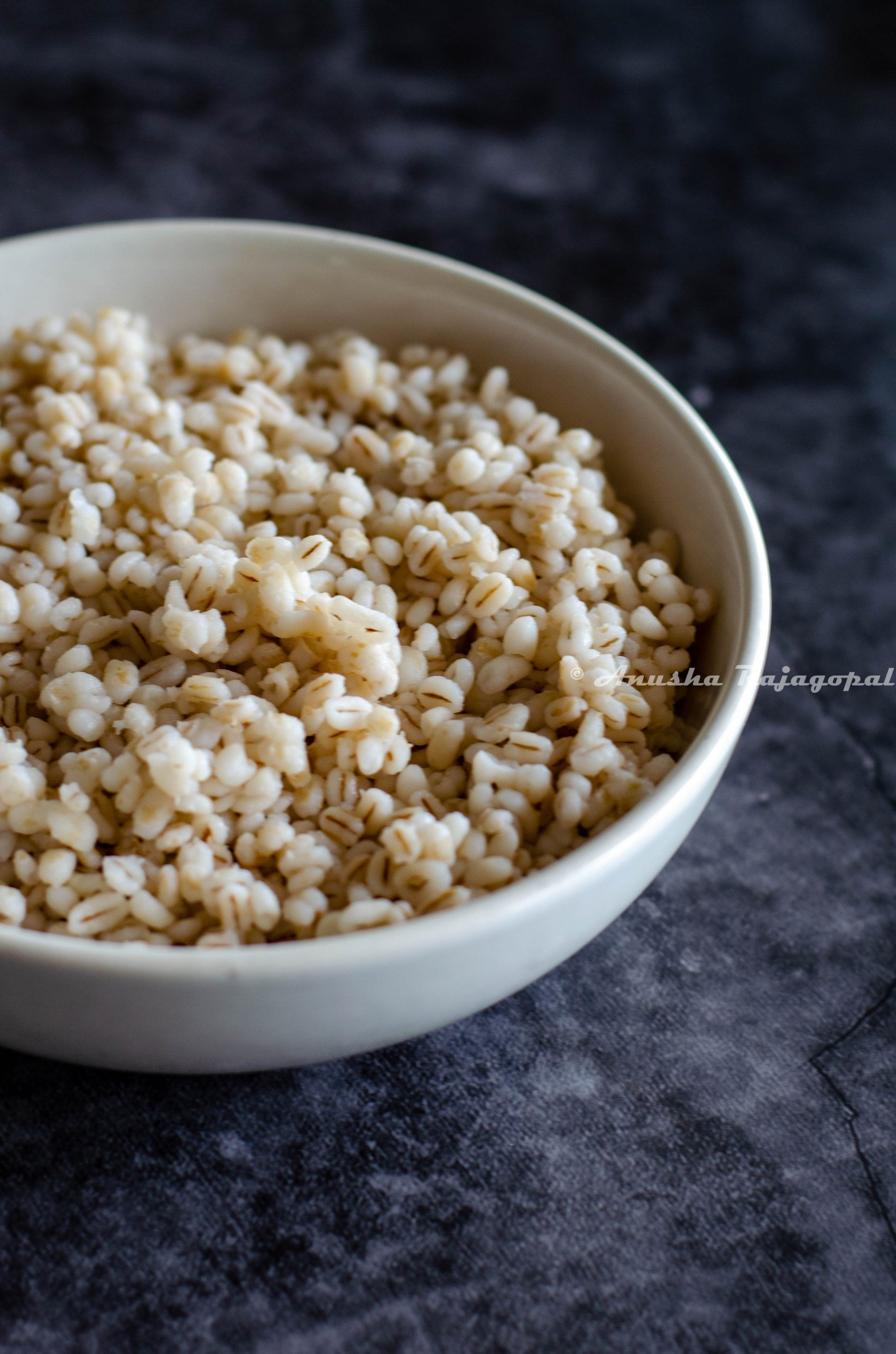 pearl barley cooked in instant pot and served in a white bowl placed over a grey backdrop