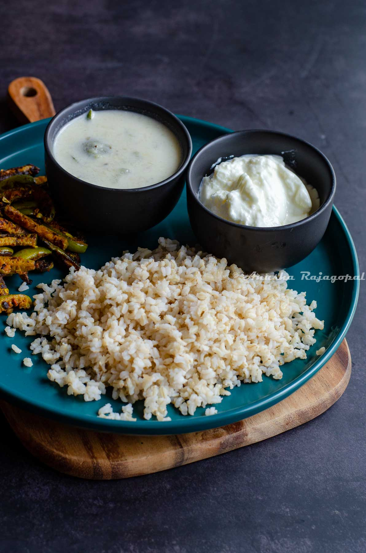 brown sona masoori rice cooked in instant pot served in a grey bowl with curry and veggies
