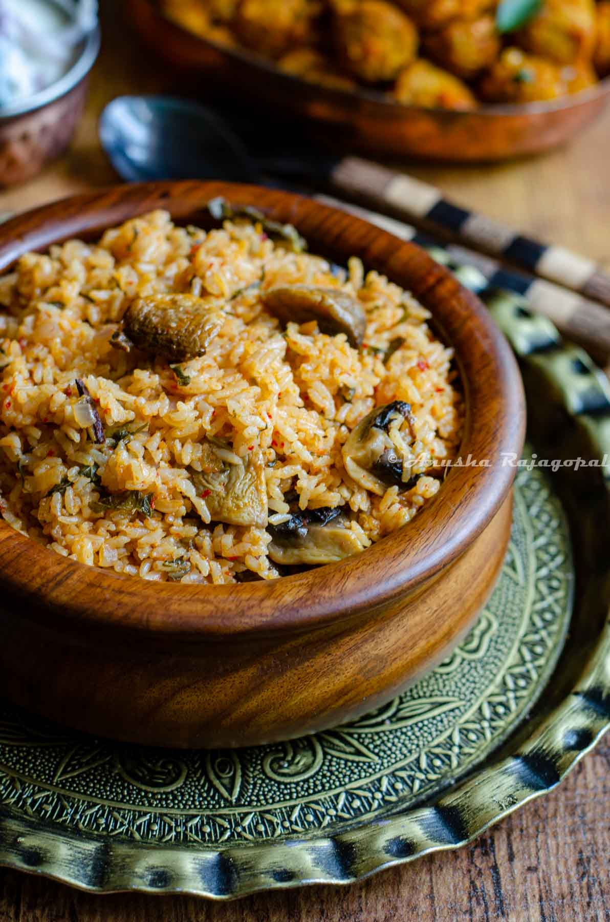 instant pot seeraga samba biryani served in a wooden handi bowl with cutlery by the side.