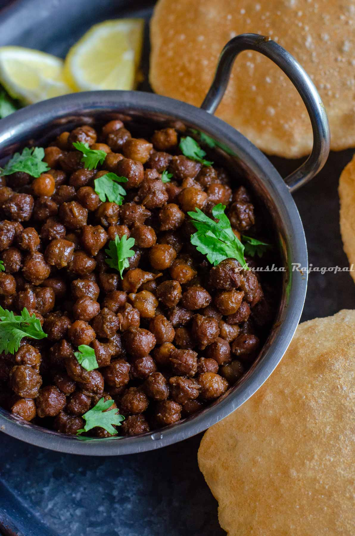Kala chana made in Instant pot served in a steel pan with pooris placed on a black platter